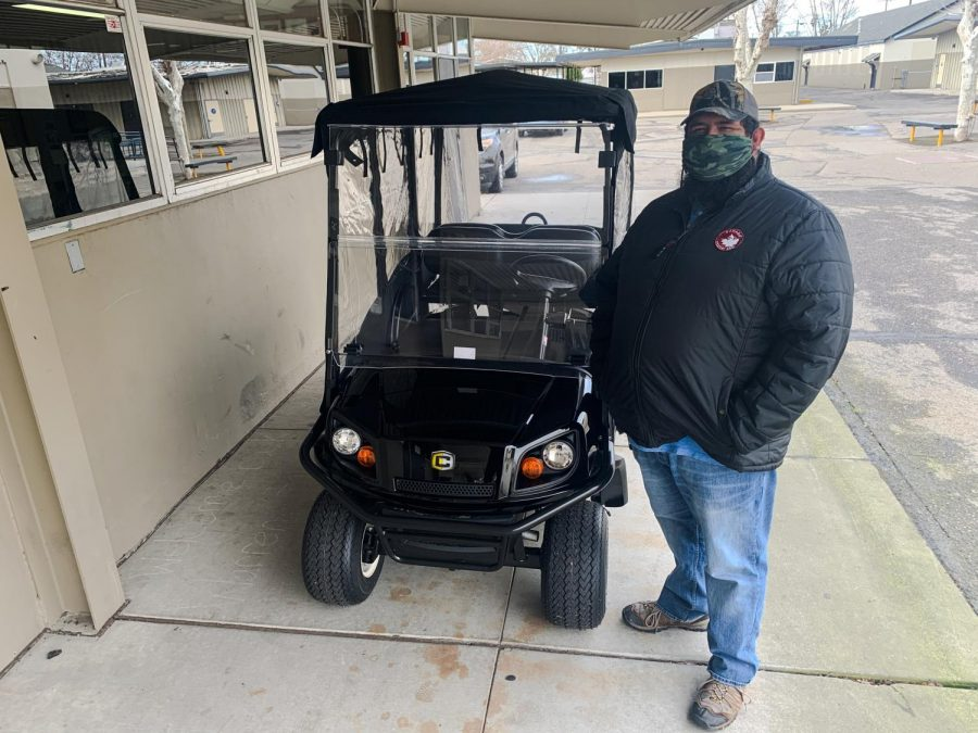Julian+Padilla%2C+HHS+campus+supervisor%2C+stands+next+to+one+of+two+new+fully+electric+golf+carts+the+school+has+recently+received+through+a+grant.